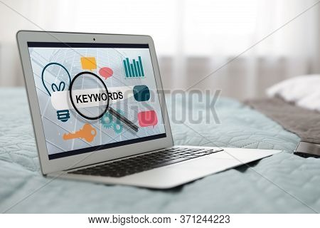 Keywords Research Concept. Modern Laptop With Search Bar And Icons On Bed Indoors