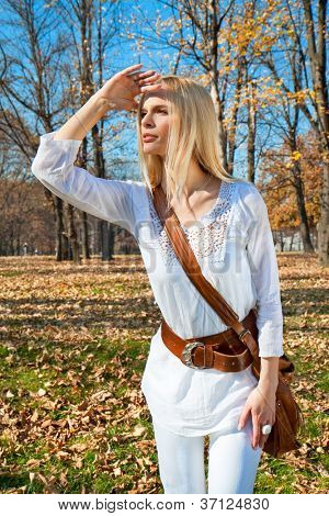 Young woman looks askance at the autumn colored park