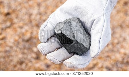 Miner Hand Holding Iron Stone, Metallic Iron Pyrite, Steel, Used In Heavy Industrial Production. Min