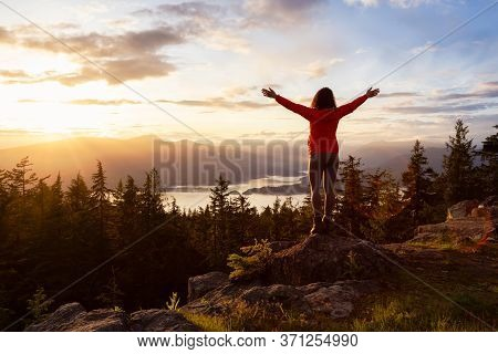 Adventure Girl On Top Of A Mountain With Canadian Nature Landscape In The Background During Colorful