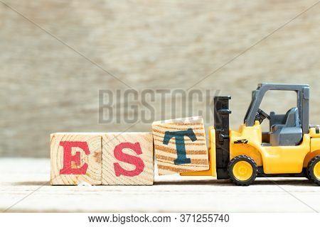 Toy Forklift Hold Letter Block T To Complete Word Est (abbreviation Of Established, Estimated, Easte