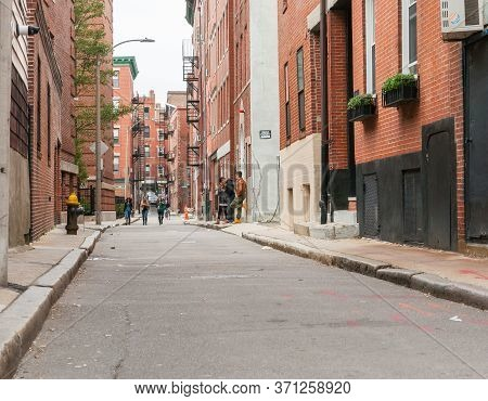 Boston Usa - October 14 2019; Boston Backstreet Street Scene With Young People Below Red Brick Build