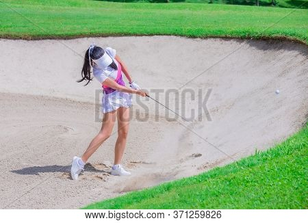 Thai Young Woman Golf Player In Action Swing In Sand Pit During Practice Before Golf Tournament At G
