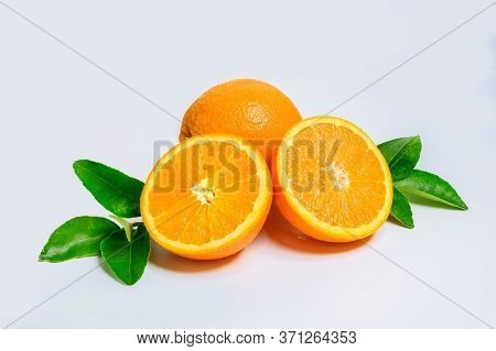 Two Fresh Orange Slices And One Orange Fruit With Green Leaf Isolated On White Background.