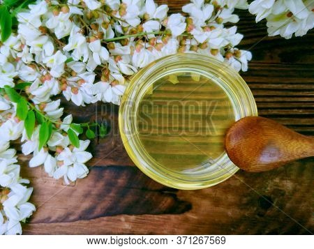 White Acacia Honey Jar, Flowers & Green Leaf On Wooden Background. Spring Acacia White Flowers. Robi
