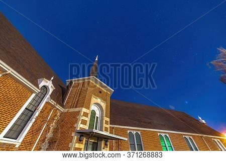 Facade Of A Church In Provo Utah With Brick Wall Arched Windows And Steeple