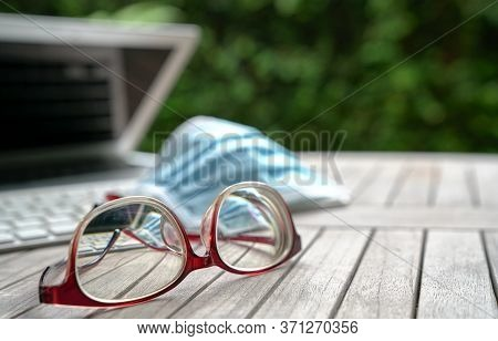Medical Face Mask On Top Of Computer Laptop Keyboard With Spectacles On Table. Focus On Spectacles.