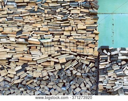 Firewood Stacked In A Woodpile Near The Green Wall Of The Barn. Preparing For The Winter
