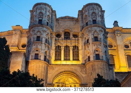 Cathedral Of Malaga With Night Yellow Illuminating Lights In Malaga, Spain. Old Architecture In Anda