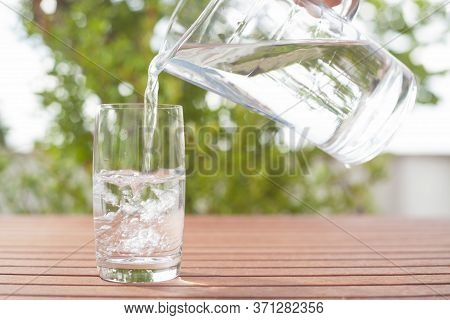 Drinking Water Flowing From A Glass Jug Into A Glass - Background With Plants
