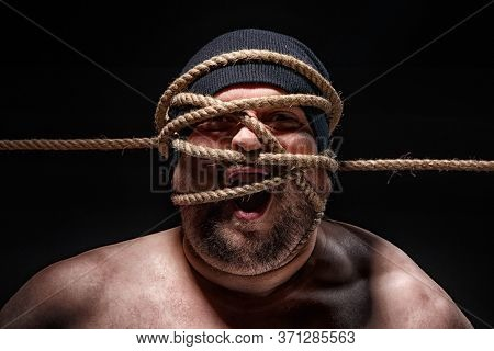 Photo Of Binded Fat Man With Rope On Face