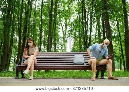 A Bald Man In A Medical Face Mask Is Sitting On A Bench Keeping A Social Distance With A Woman Sitti