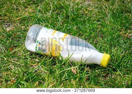 Krakow, Poland 10.03.2020: Discarded Milk Bottle On The Green Grass. Environmental Pollution. Recycl