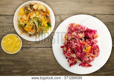 Herring Under A Fur Coat On A White Plate. Herring Under A Fur Coat On A Wooden Background. Herring,