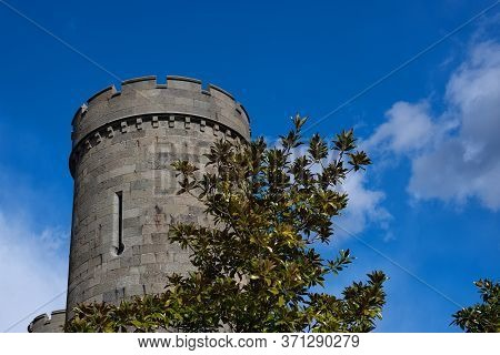 Ancient Round Stone Tower With Battlements With Blue Sky And White Clouds Background And Green Magno