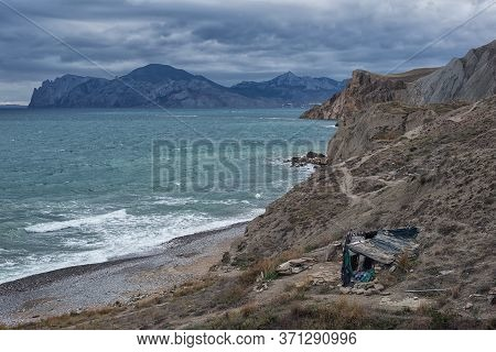 A Dilapidated Shack On The Shore Of A Gloomy Winter Sea In The Crimea