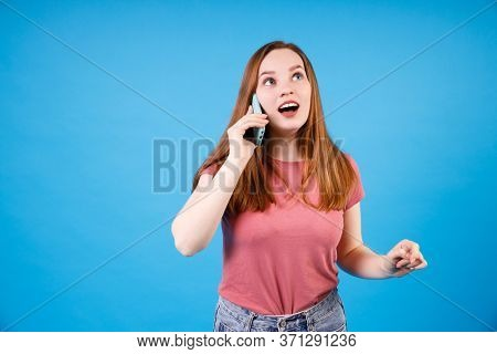 Girl with surprised expression talking at the phone. Ginger girl in pink t-shirt and jeans posing isolated on blue