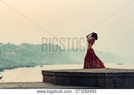 A Beautiful Indian Woman In A Red Sari, Dancing Alone On The Street. In The Background, There Is A R
