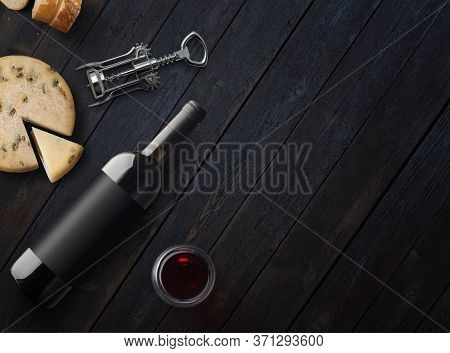 Red Wine Bottle With Cheese, Corkscrew And Wineglass On A Dark Wooden Background With Copy Space. Wi