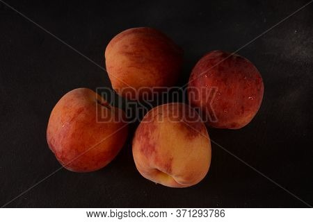 Peaches On Dark Background. Composition With Ripe Juicy Peaches. Harvest Of Peaches For Food Or Juic