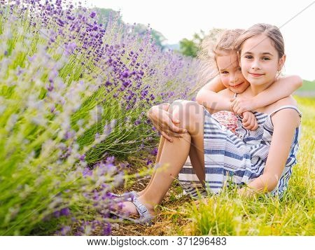 Two Girls Sister Sit Between Lavender Fields In Provence. Violet Lavender Fields Blooming In Summer