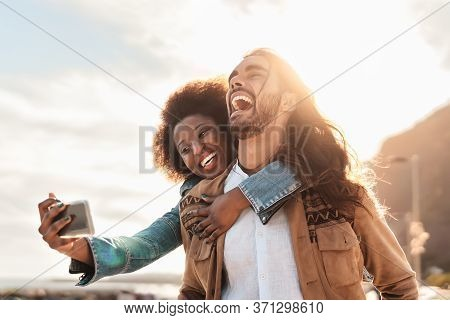 Happy Smiling Couple Taking Selfie With Mobile Smartphone Outdoor - Young Trendy People Having Fun D