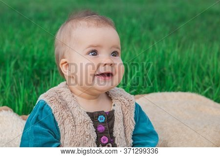 toothless baby in a multi-colored dress sitting on a bedspread on lawn