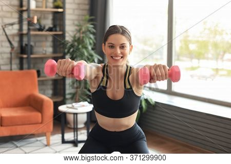 Beautiful Slim Fitness Woman Crouches With Dumbbells. Sport, Healthy Lifestyle. Girl Goes In For Spo