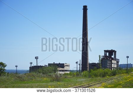 Buildings And Chimney Of An Abandoned Factory. Abandoned Factory On The Outskirts Of The City. Visib
