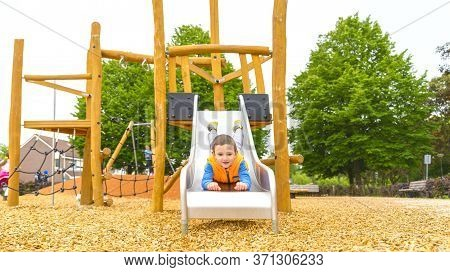 The Boy Climbing And Sliding On Slide In The Playground. Happy Children Playing And Having Fun At Pl