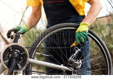 Man Lubricating Bicycle Chain And Maintaining For The New Season