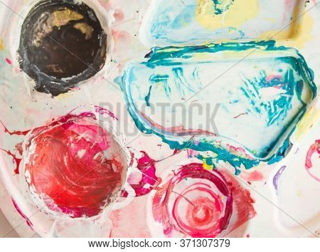Closeup Of Stained Palette On A White Background. Mixing Paints. Colorful Mix Of Acrylic Vibrant Col