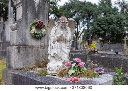 Stoned Angel On The Tombstone In The Public Cemetery, Grave Sculpture, Rip