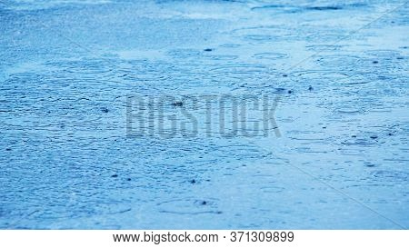 Puddle With Raindrops And Circles On The Surface Of The River Water, Background Puddle Rain
