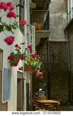 House With Flowers In A Dark Alley. Image Of A Small European City