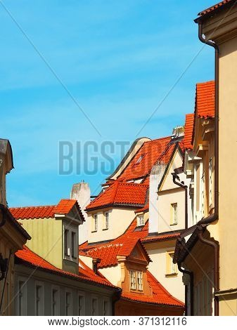 Red Tiled Roofs And Narrow Streets Of Old Prague. Traditional Bohemian Buildings In The Streets Of P