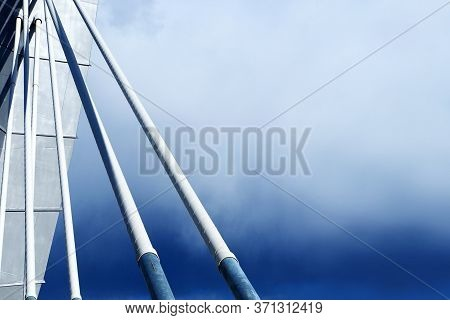 Ropes And Support From Cable Stayed Bridge On Cloudy Blue Sky Background