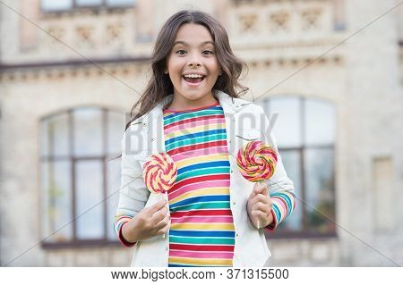 Stylish Schoolgirl Hold Lollipop Candy. Child At Candy Shop. Spring Fashion Style. Cheerful Small Gi