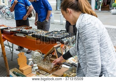 Female Customer Checking Items Sold At Flee Market.