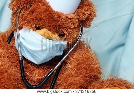 Portrait Of Tired Teddy Bear Doctor With Protective Medical Mask And Stethoscope. Teddy Bear Sits Wi