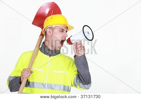 Worker with a spade screaming into a bullhorn
