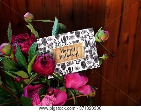 Close-up Of Pink Peonies Flowers And Vase On Wooden Background With Happy Birthday Card. The Photo W