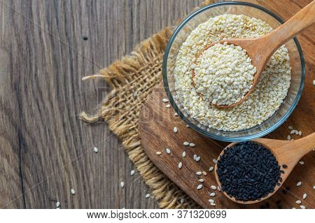 White Sesame Seeds In A Wooden Spoon And Black Sesame On Wood Block. White Sesame Helps To Strengthe
