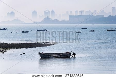 Various Small Boats Moored Offshore In Fushan Bay With A Hazy View Of The City Of Qingdao China, Sha