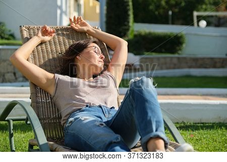 Mature Adult Woman Resting Lying In An Outdoor Chair On The Lawn. Rest, Relaxation, Lifestyle, Vacat