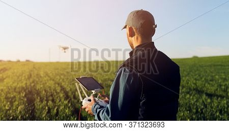 Caucasian Man Farmer In Hat Standing In Green Wheat Field And Controlling Of Drone Which Flying Abov