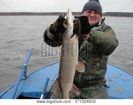 Fishing. Fisherman And Trophy Pike. Fisherman In A Boat On The River