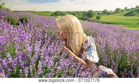 Portrait Of Smiling Young Woman Smelling Flowers On Lavender Field In Provence