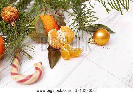 Slices Of Fresh Tangerine, Whole Tangerines, Spruce Branches, Lollipop, Golden Christmas Ball On A W