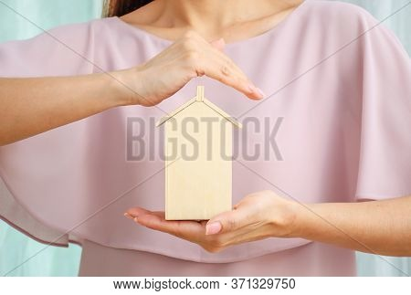 Model Of A House On One Hand. A Second Hand Is Held Protectively Over It.